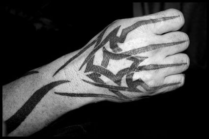 Man With Black Ink Tribal Tattoo On Right Hand